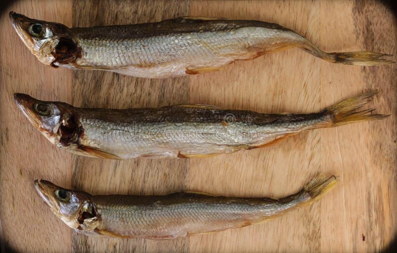 Sonnengetrocknete Fische, gesalzene Schmelze über hölzernem Hintergrund, Draufsicht, Kopienraum stockbilder