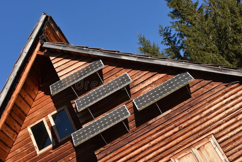 Sonnenkollektor auf einem Holzhaus stockbild