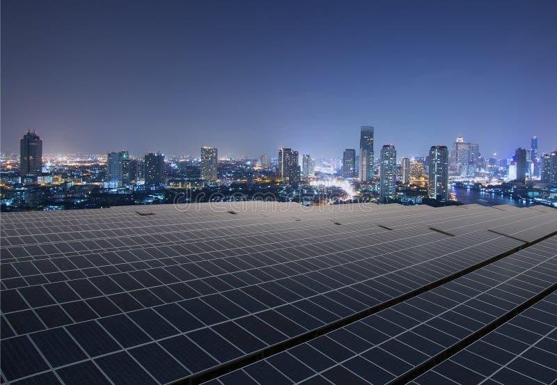 Sonnenkollektoren mit Dämmerungsstadt stockbilder