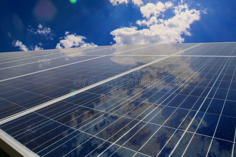 Sonnenkollektoren mit Wolkenreflexion stockfotos