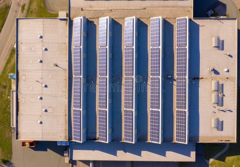 Sonnenkollektoren oder Photovoltaik-Kraftwerk auf dem Dach eines Fabrikgebäudes stockbild