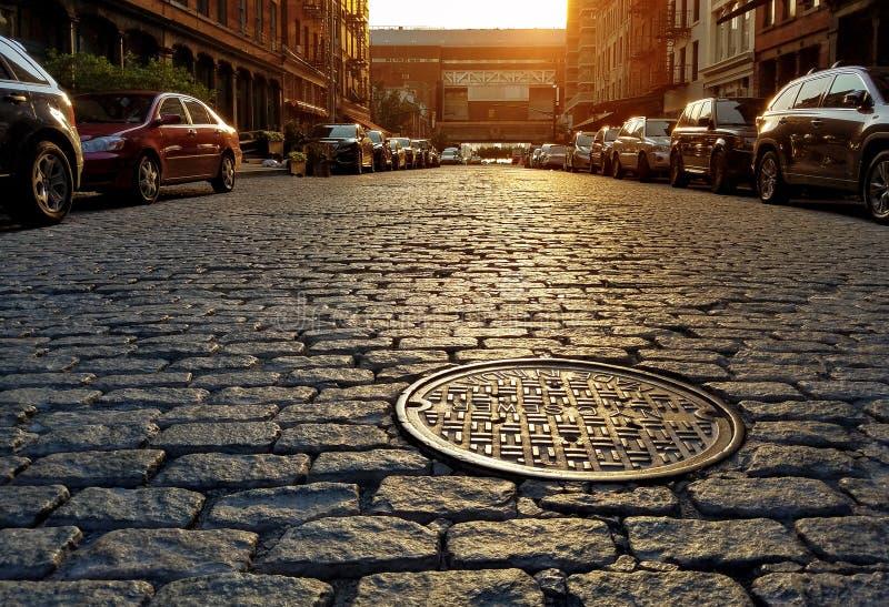 Sonnenlicht, das auf einer Kopfsteinstraße und -Kanaldeckel in New York City glänzt lizenzfreies stockfoto
