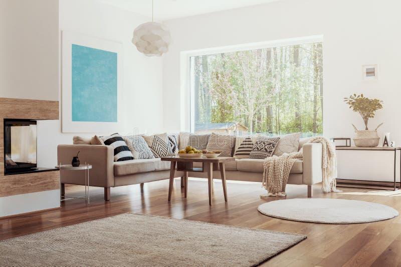 Sonnenlicht, das durch ein großes Fenster in einen weißen und beige Wohnzimmerinnenraum mit Obstschalen auf einem Holztisch kommt lizenzfreie stockbilder