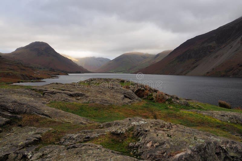 Sonnenlicht fällt auf eine See-Bezirksgebirgsseite aus einem bewölkten Himmel heraus, der gegen den dunklen See und das Tal, Cumb stockfoto