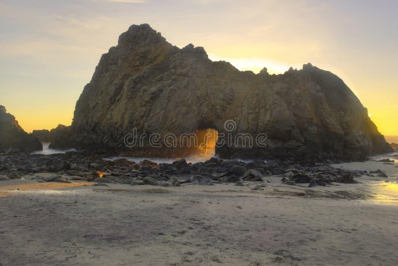 Sonnenlicht strömt durch Schlüsselloch/Trapezfehlerbogen, Pfeiffer-Strand stockfotografie