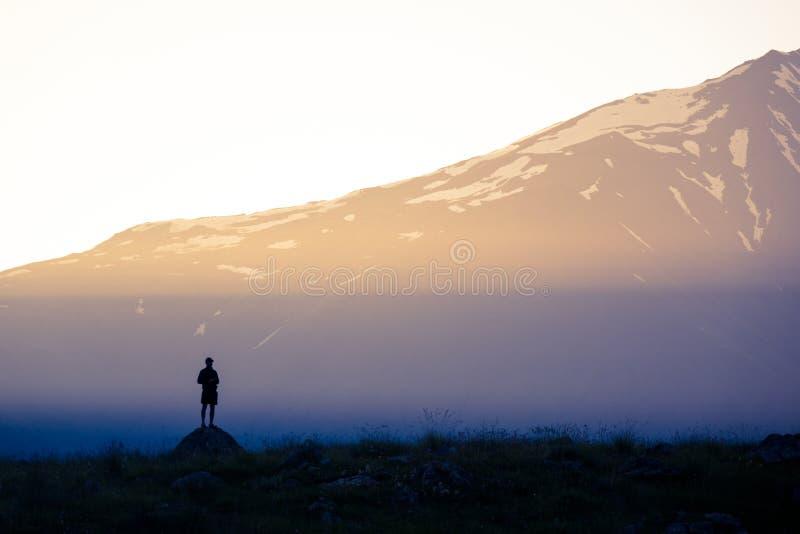 Sonnenlicht und Schattenbild eines Mannes auf dem Hintergrund der Berge stockfotos