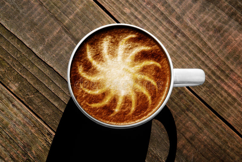 Sonnenschein Latte-Kunst in der Schale auf Rost farbigem Holztisch lizenzfreies stockbild