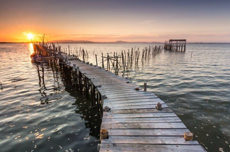 Sonnenschein von einem Sonnenuntergang auf einem alten Pier lizenzfreies stockfoto
