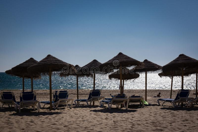 Sea beach, umbrella deck chair in Cadiz noon sunshine. Spain Andalucia, sea beach, umbrella, deck, chair in Cadiz noon sunshine royalty free stock photo