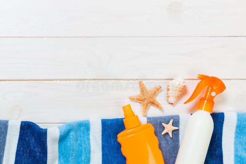 Sonnenschutzflaschen mit Seestern und blauem Handtuch auf weißem Holztisch mit Kopierraum Reisezubehör für das Gesundheitswesen - lizenzfreie stockfotografie