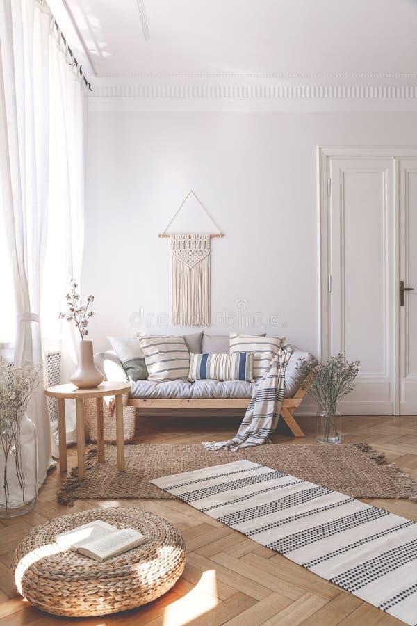 Sonnenstrahlen auf einem Weidenosmane- und Fischgrätenmusterboden eines beige Wohnzimmerinnenraums mit einem hölzernen Sofa und K stockfotografie