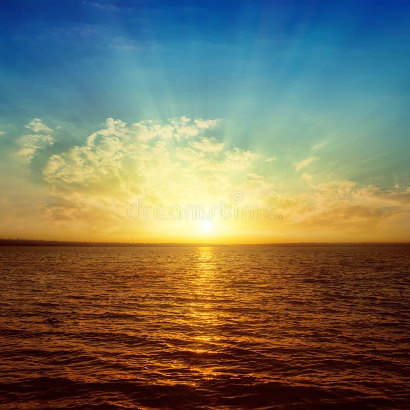 Sonnenstrahlen in den Wolken über orange Wasser lizenzfreies stockfoto