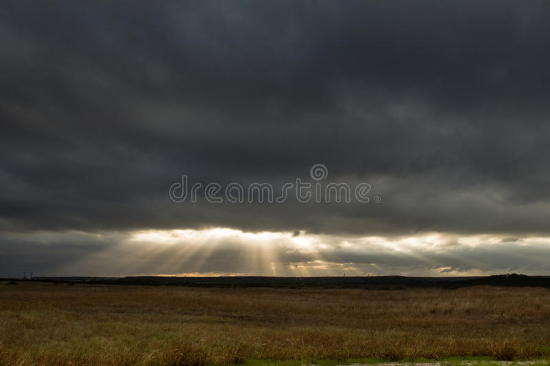 Sonnenstrahlen durch dunkle Wolken stockbilder