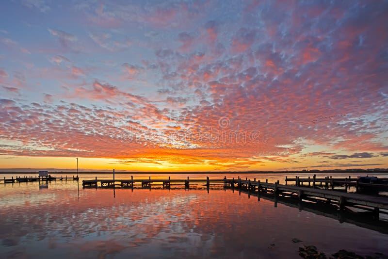 Sonnenuntergang über Anlegestelle und Fluss stockbilder