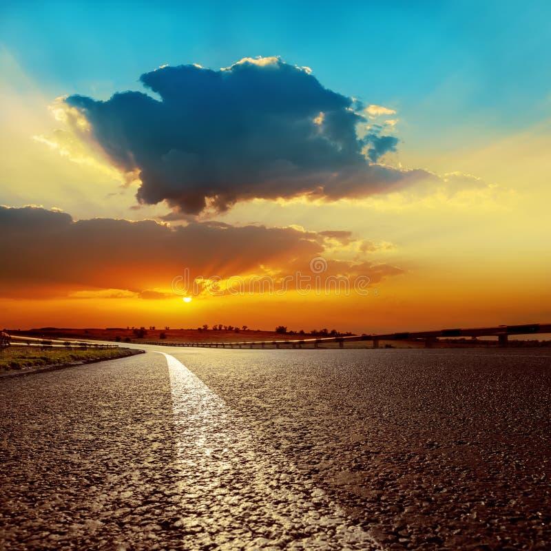 Sonnenuntergang über Asphaltstraßenahaufnahme lizenzfreie stockfotos
