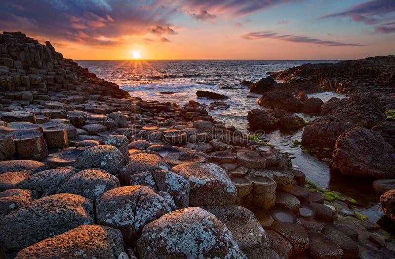 Sonnenuntergang über Basaltsäulen riesiger ` s Damm, Grafschaft Antrim, Nordirland stockfotos
