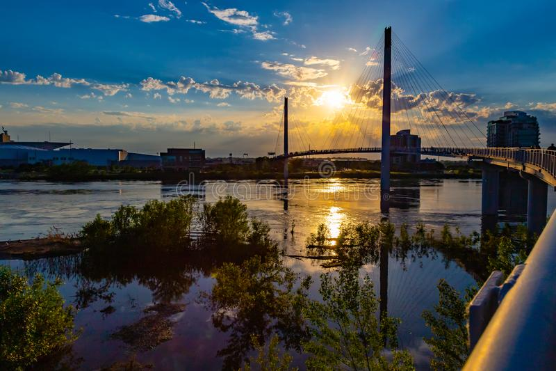 Sonnenuntergang über Bob Kerrey Pedestrian-Brücke und dem geschwollenen Missouri bei Omaha Riverfront lizenzfreies stockbild
