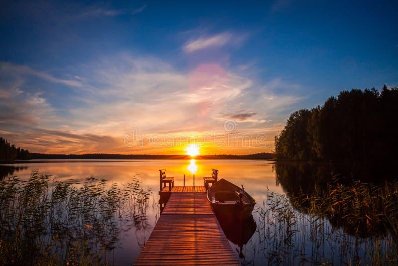 Sonnenuntergang über dem Fischenpier am See in Finnland lizenzfreie stockbilder