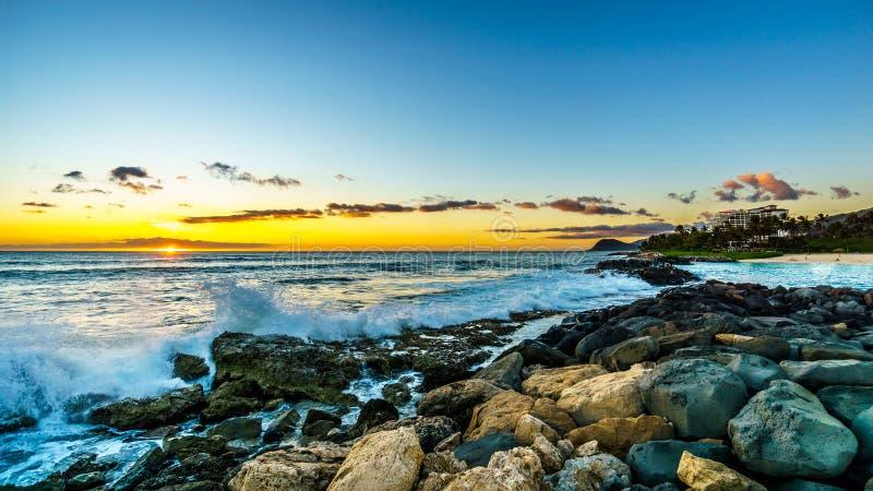 Sonnenuntergang über dem Horizont mit einigen Wolken und den felsigen Ufern der Westküste von Oahu lizenzfreie stockfotografie