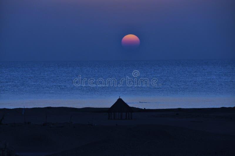 Sonnenuntergang über dem Meer durch den Strand lizenzfreie stockfotografie