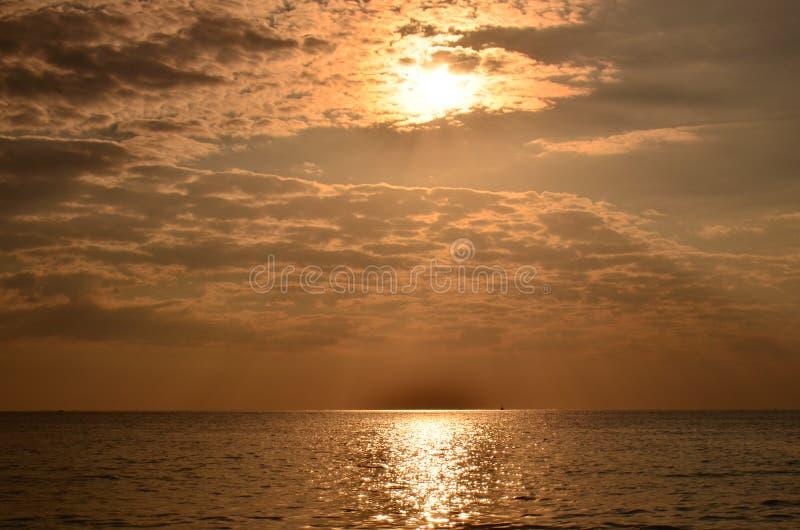 Sonnenuntergang über dem Meer Goldsonnenuntergang, -meer und -wolken Schöner goldener orange Sonnenuntergang über dem Ozean lizenzfreie stockfotografie