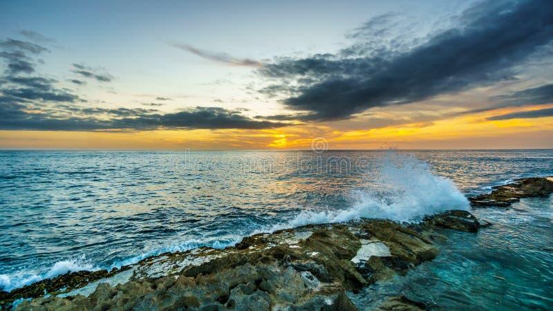 Sonnenuntergang über dem Pazifischen Ozean mit den Wellen, die auf Rocky Shoreline unter buntem Himmel zusammenstoßen lizenzfreie stockbilder