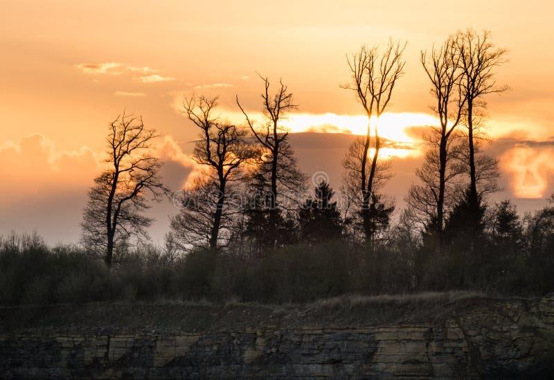 Sonnenuntergang über dem Wald und der steilen Klippe des Steinbruchs stockbilder