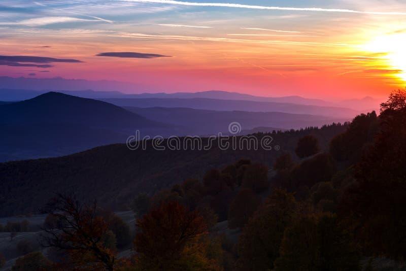 Sonnenuntergang über den Hügeln bedeckt mit Herbstbäumen lizenzfreies stockfoto