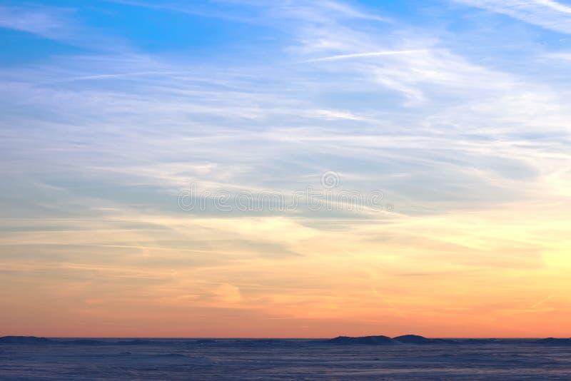 Sonnenuntergang über der schneebedeckten Wüste Blauer Himmel der Leuchtorange stockbild