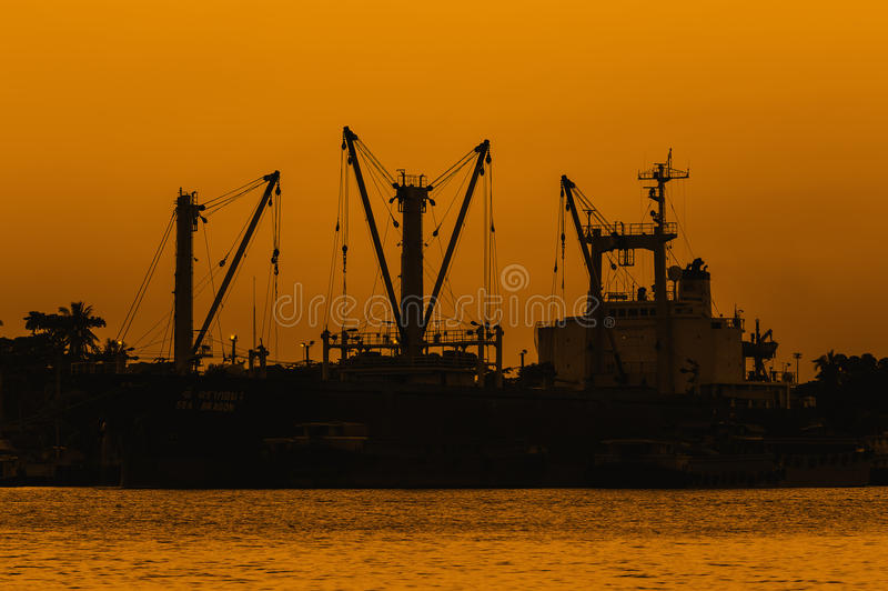 Sonnenuntergang über Dockschiff oder -hafen nahe Fluss stockbild
