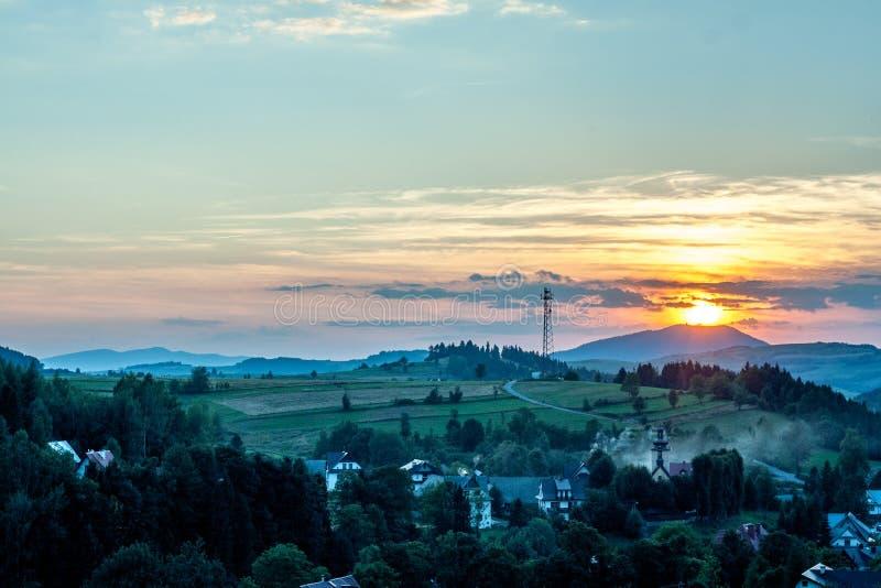Sonnenuntergang über Dorf und grünen Hügeln lizenzfreies stockfoto