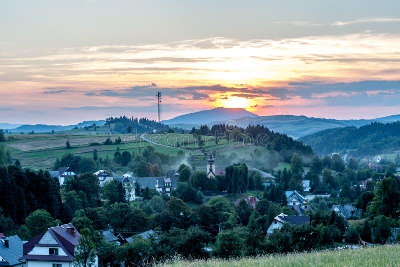 Sonnenuntergang über Dorf und grünen Hügeln lizenzfreie stockfotos