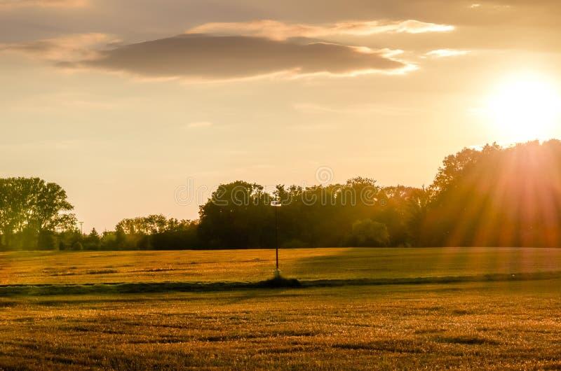 Sonnenuntergang über einem Feldweg mit einer Lampe stockbild
