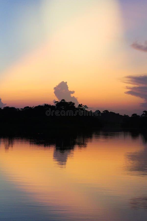 Sonnenuntergang über einem Fluss mit Reflexionen von Bäumen gegen das Licht stockfoto