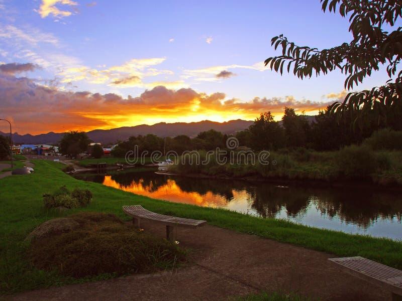Sonnenuntergang über einem ruhigen Strom stockfotos