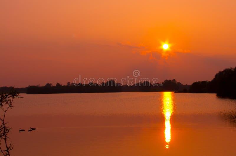 Sonnenuntergang über einem See im cambridgeshire stockbild