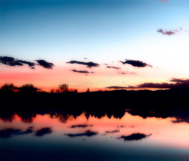 Sonnenuntergang über einem See mit Reflexionen im Wasser lizenzfreie stockfotografie