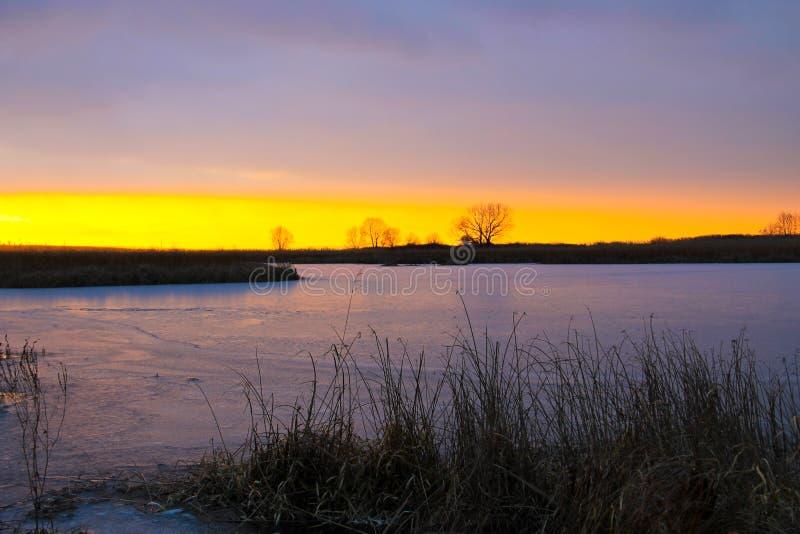 Sonnenuntergang über einem Winterfluß stockfoto