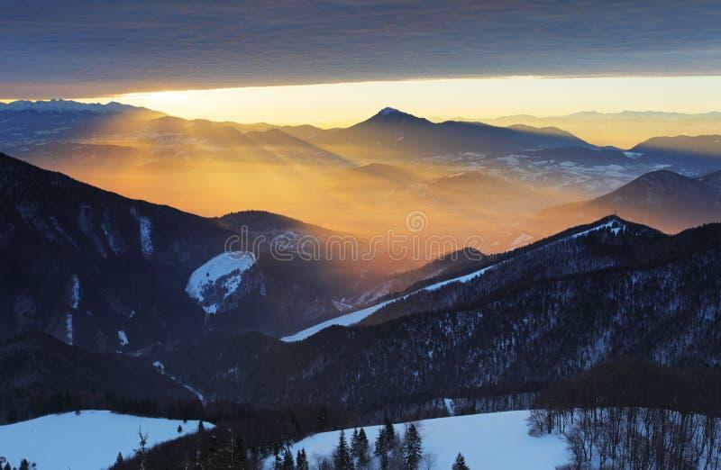 Sonnenuntergang über Farbgebirgsschattenbild mit Strahlen lizenzfreie stockfotografie