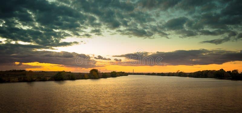Sonnenuntergang über Flussufer lizenzfreie stockfotos