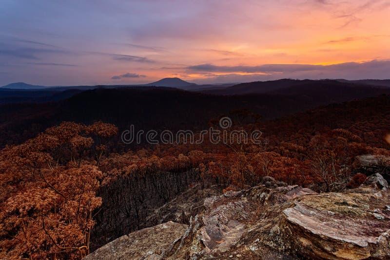 Sonnenuntergang über gecharterte Landschaft nach Waldbränden in Australien stockbilder