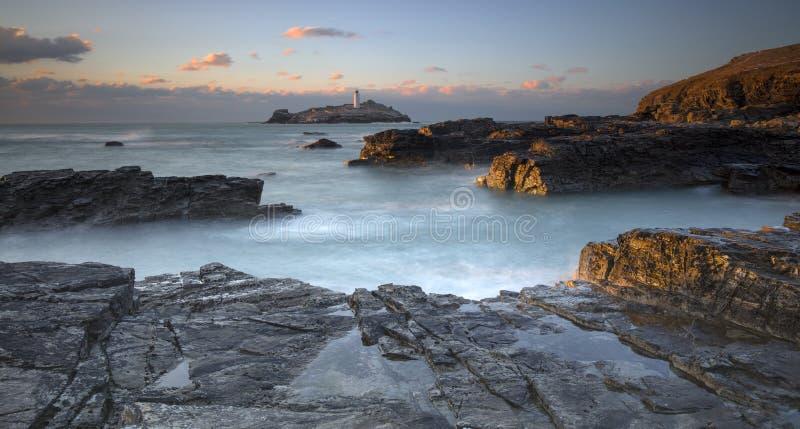 Sonnenuntergang über Godrevy-Leuchtturm auf Godrevy-Insel in St. Ives Bay mit dem Strand und Felsen im Vordergrund, Cornwall Groß stockfotos