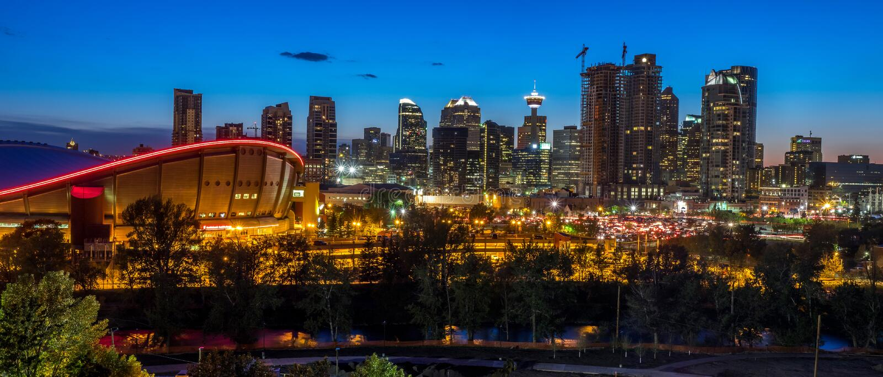 Sonnenuntergang über im Stadtzentrum gelegenem Calgary und Saddledome lizenzfreie stockfotografie