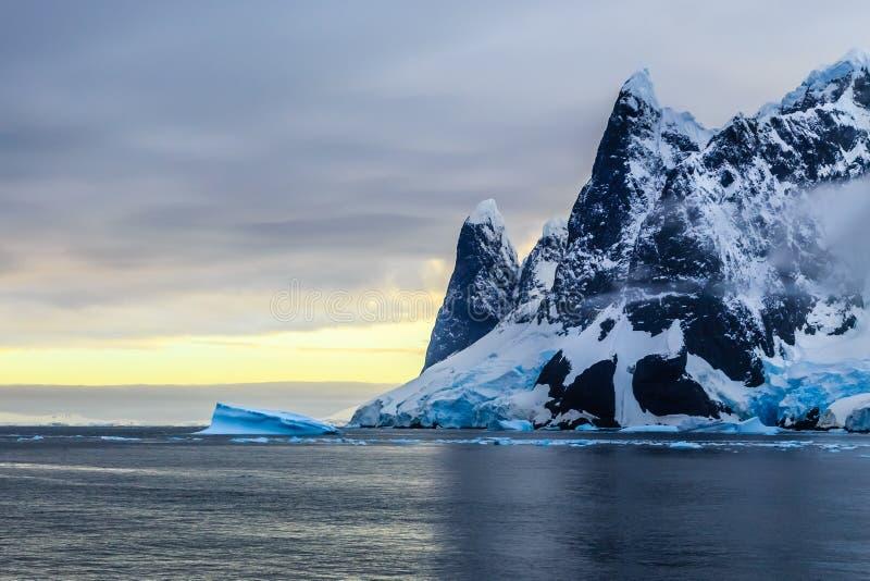 Sonnenuntergang über Klippen, blauem Gletscher und treibendem Eisberg mit Wasser lizenzfreies stockbild