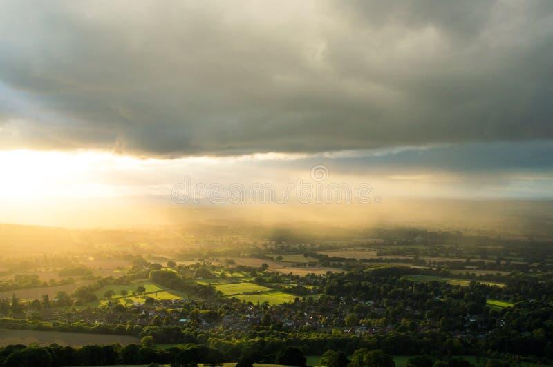 Sonnenuntergang als Sonnenstrahlen leuchten der englischen Landschaft an einem Sommerabend mit dunklen Wolken oben lizenzfreie stockfotos