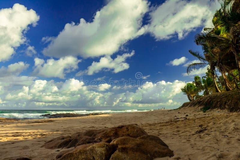 Sonnenuntergang auf dem einsamen Strand Der Himmel, der durch weiße Wolken bevölkert wird, kontrastiert zum Blau des Meeres lizenzfreie stockfotos