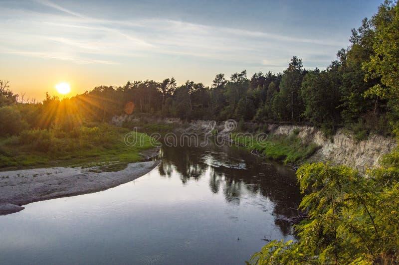Sonnenuntergang auf dem Hintergrund einer steilen Kurve im Fluss mit einem Sandstrand mit wachsendem Wald River Western Bug in Eu stockfoto
