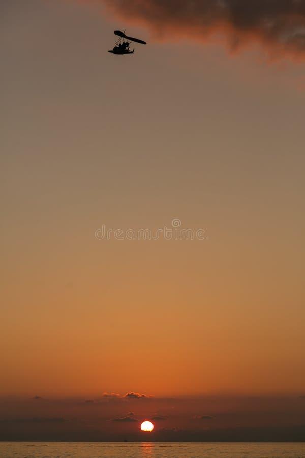 Sonnenuntergang auf dem Horizont gegen das Meer und den Himmel und hochfliegendes im Himmelgleitschirm stockfoto