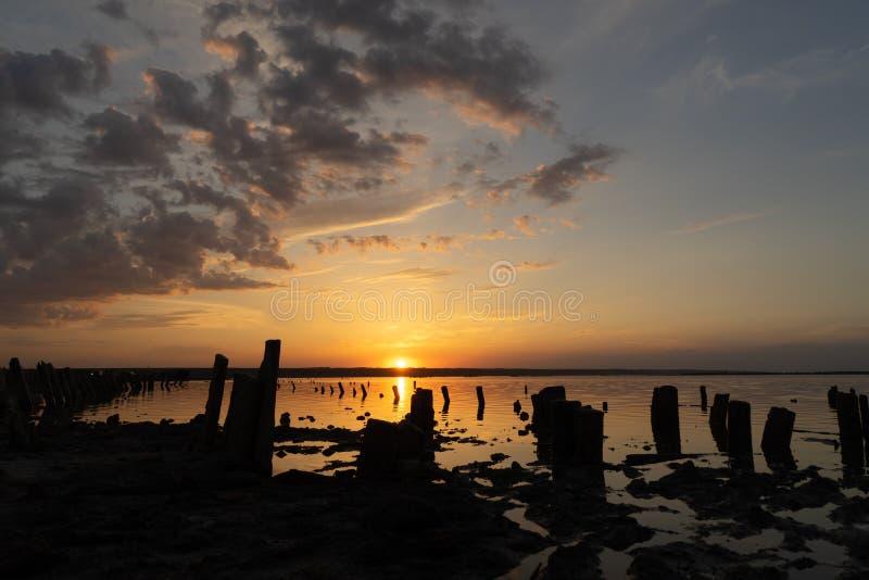 Sonnenuntergang auf dem Kuyalnik Liman odessa ukraine Alte Klotz sind vom wasser- die Überreste eines alten Piers sichtbar lizenzfreie stockfotos
