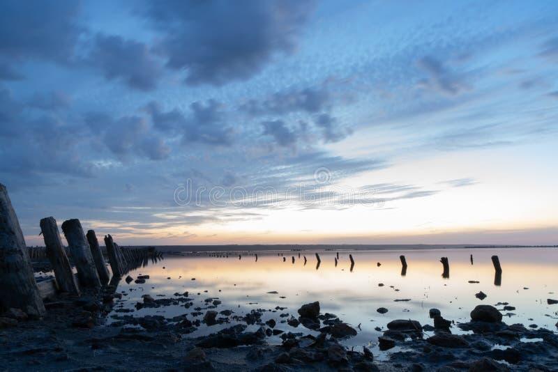 Sonnenuntergang auf dem Kuyalnik Liman odessa ukraine Alte Klotz sind vom wasser- die Überreste eines alten Piers sichtbar lizenzfreies stockbild